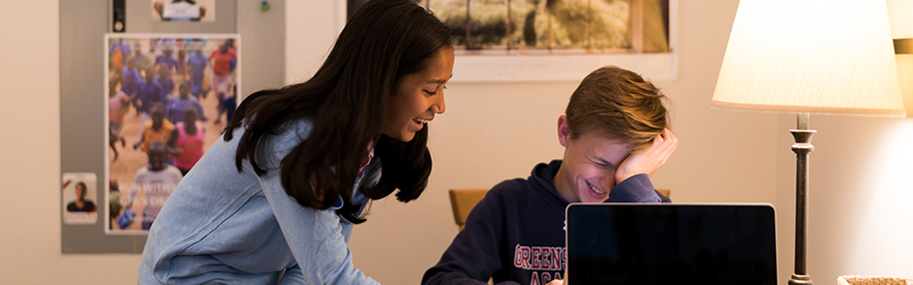 Students working together and laughing at computer.